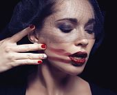 foto of grieving  - beauty brunette woman under black veil with red manicure close up - JPG