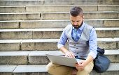 stock photo of handsome  - Handsome hipster modern businessman using laptop in the city
