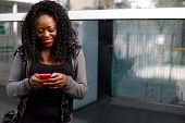 stock photo of sms  - Young African woman sending an sms on her mobile smiling as she types in the text with her thumbs on the touch screen in front of an urban building - JPG