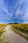 foto of wispy  - Wispy clouds over a Gravel track leading to Badbury Rings Iron age fort - JPG