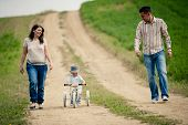 stock photo of tricycle  - Happy family with little boy on wooden tricycle walking in ntaure - JPG