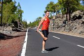 foto of thighs  - Runner man stretching thigh and legs after running on mountain forest road in - JPG