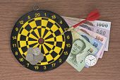 foto of projectile  - Dart target clock and Money over wooden table - JPG