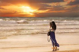 picture of hair blowing  - A woman with a white blouse and purple skirt blowing in the breeze is standing on the beach - JPG