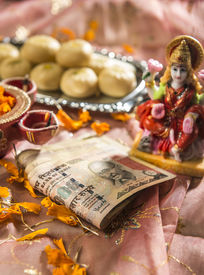 stock photo of laxmi  - Indian rupees bank notes in Diwali puja with a Goddess of wealth  - JPG