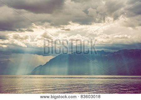 Beautiful sun rays falling through heavy clouds on the mountains and the lake.  Color toned image.