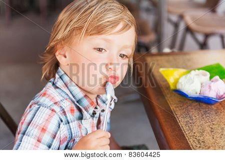 Adorable toddler boy eating ice cream in a cafe on a very hot day