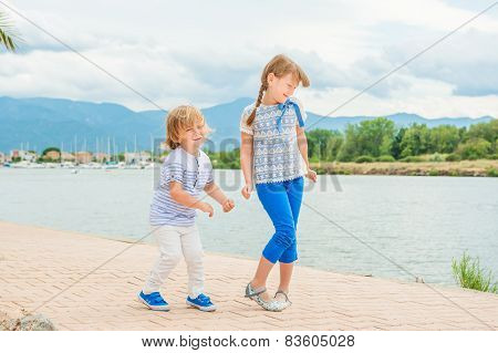 Adorable kids having fun outdoors on a nice sunny summer day