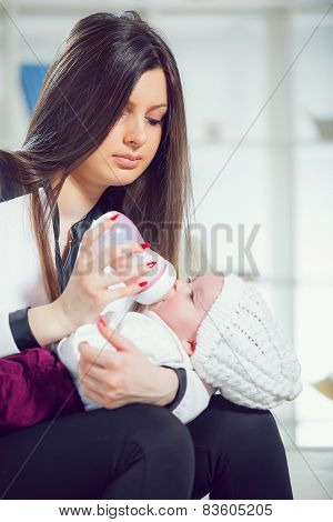 Young mother at home feeding their new baby girl with a milk bottle