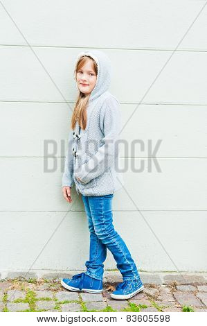 Outdoor portrait of a cute little girl wearing grey knitted parka, jeans and blue shoes
