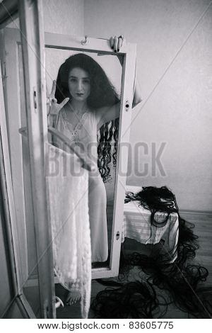 creepy young woman with long curly hair in scary room