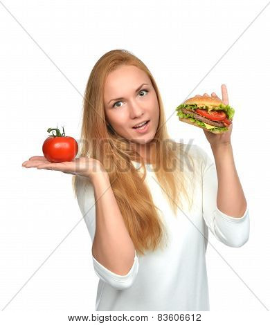Woman Comparing Tasty Unhealthy Burger Sandwich In Hand And Tomato