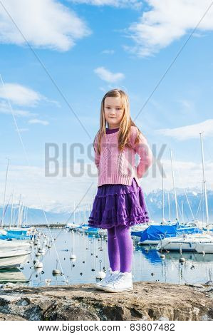 Outdoor portrait of a cute little girl in a port on a nice day, wearing pink pullover and purple ski