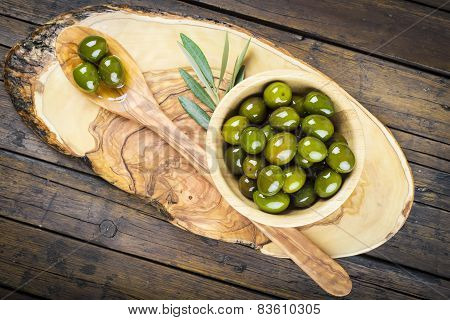 Wooden Bowl And Spoon With Green Olives And Olive Oil