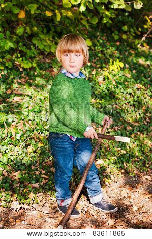 Outdoor portrait of a cute little boy wearing green pullover