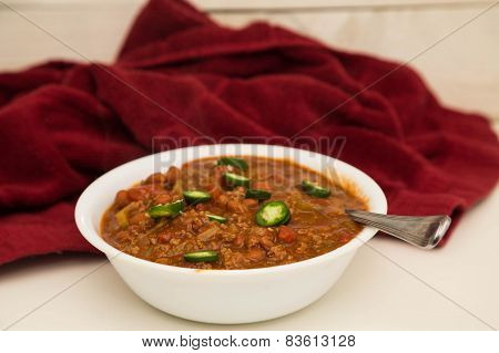 White Bowl Of Chili With Sliced Jalapenos And Red Towel