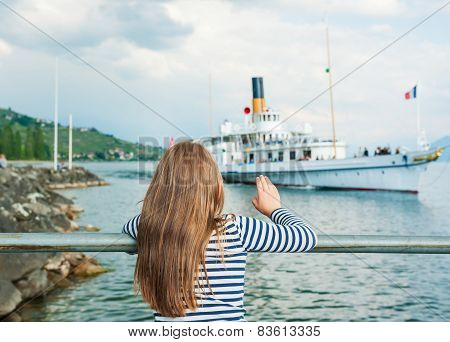 Cute little girl welcomes a sailing boat