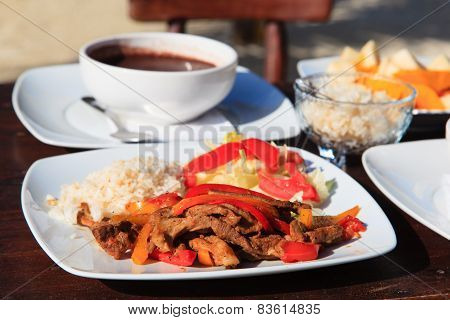 meat, vegetables, rice with soup and fruit salad