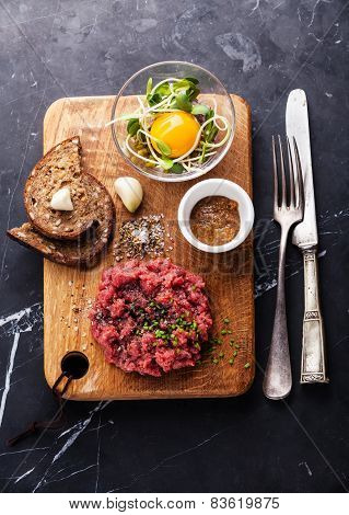 Beef Tartare With Salad And Garlic Toasts On Dark Marble Background