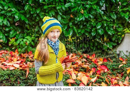 Autumn portrait of a cute little girl playing outddoors with leaves