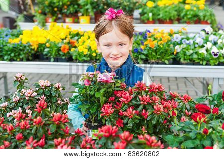 Adorable little girl choosing flowers in flower shop on early spring