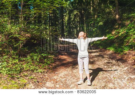 Outdoor portrait of a kid girl with arms open wide
