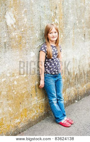 Outdoor portrait of a cute little girl, wearing jeans and beautiful red moccasins