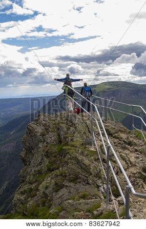 Three men on a mountain top over the precipice