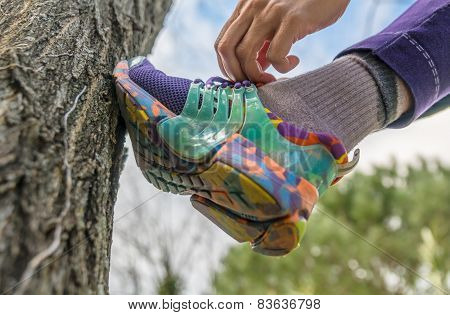 Woman Tying Up Shoelases Leaning With The Shoe On Tree