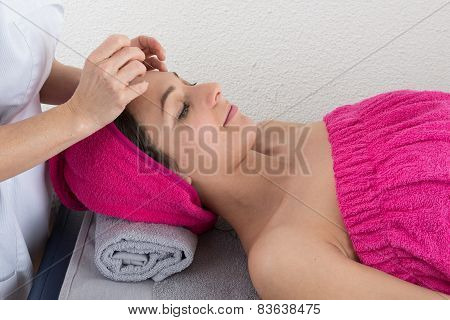 Woman Lying On Massage Table Getting Acupuncture