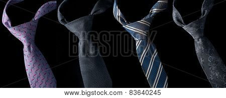 Set of four ties isolated on black background.