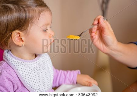 Baby eating puree from a spoon in the hand of mother
