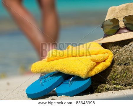 Straw Hat, Towel Beach Sun Glasses And Flip Flops On A Tropical Beach