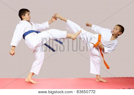 In karategi boys are beating kicks on the mats