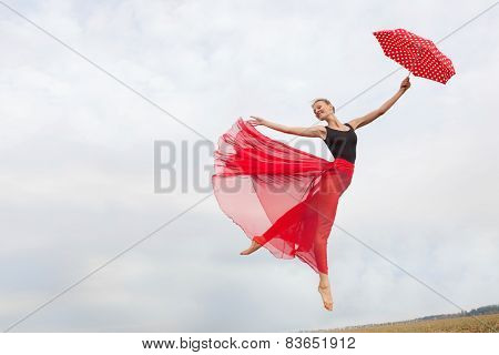 Young Woman Flying In The Sky With Red Umbrella