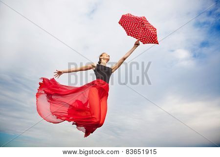 Young Woman Flying In The Sky With Umbrella