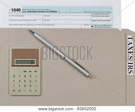 Individual Income Tax Form Inside Folder With Ink Pen And Calculator On Top