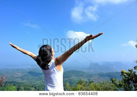 oung woman cheering open arms at mountain peak