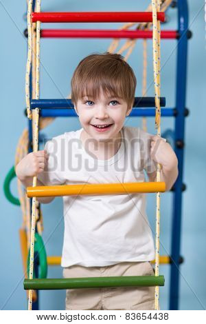 Kid boy climbing a rope ladder