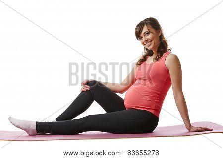 Joyful pregnant woman sitting on fitness mat