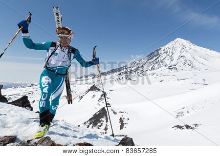Ski Mountaineer Climb To Mountain On Background Volcano With Skis Strapped To Backpack