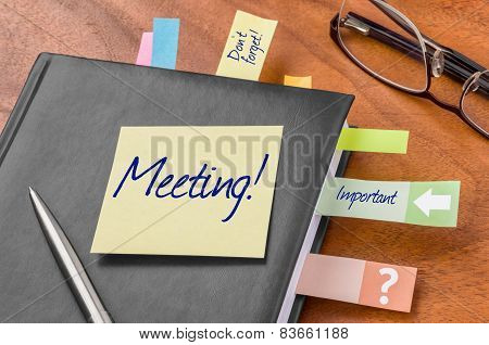 A planner with a sticky note - Meeting