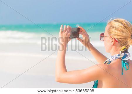 Woman taking photo on the beach.