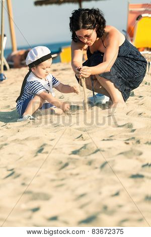 Sweet Toddler Dressed As A Sailor Sitting On A Beach And Playing With The Sand With His Mother. Phot