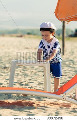 Sweet Toddler Dressed As A Sailor Standing On A Beach Near A Plastic Table And Sunbed. Photo With Un