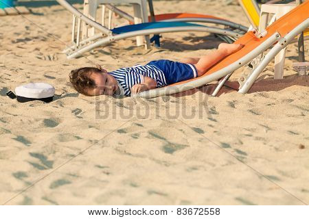 Toddler Dressed As A Sailor Lying From A Top Of A Sunbed On A Beach And Looking As He Is Drunk With