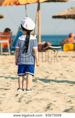 Toddler Dressed As A Sailor Standing On A Beach And Looking Around At Other People In The Background