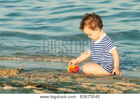 Toddler With Sailor Shirt Sitting And Playing At The Edge Of The Waves On A Beach. Photo With Untrad