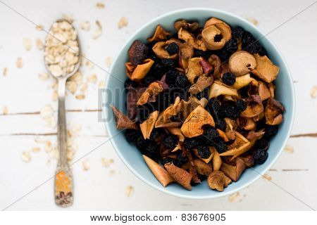 One Tablespoon Of Oatmeal Is A White Wooden Background Near Blue Plate With Dried Apples And Berries