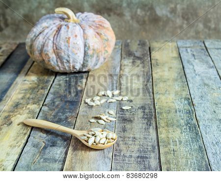 Pumpkin And Pumpkin Seeds In Wood Spoon On Wooden Background.